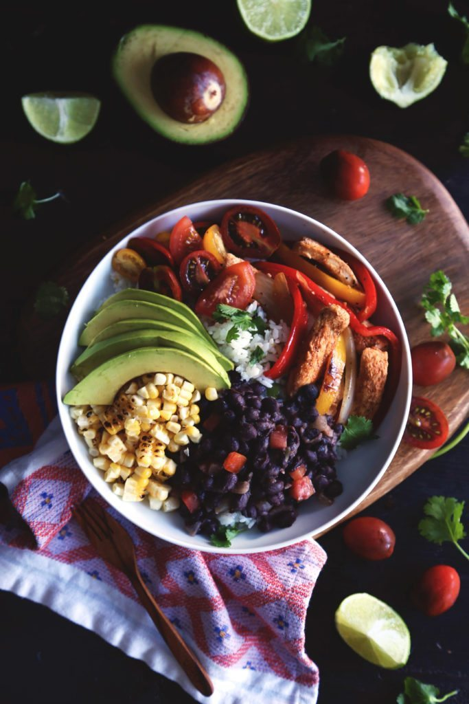 Chicken Fajita Rice Bowl   Cilantro-lime rice topped with fajita style chicken, seasoned beans, grilled corn, and fresh avocado and tomatoes. Healthy and delicious!