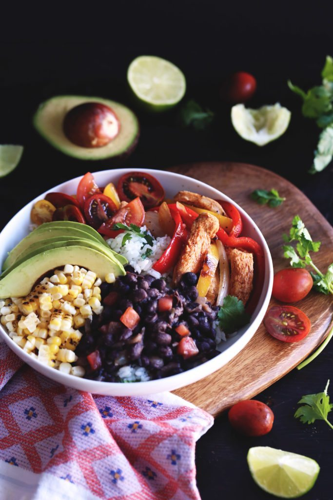 Chicken Fajita Rice Bowl | Cilantro-lime rice topped with fajita style chicken, seasoned beans, grilled corn, and fresh avocado and tomatoes. Healthy and delicious!