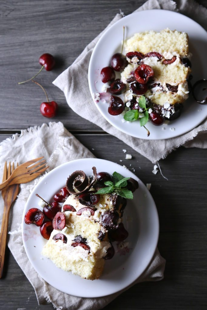 White Forest Cake | Gluten, dairy, and refined sugar free vanilla cake is topped with white chocolate buttercream, cherries, and dark chocolate ganache.