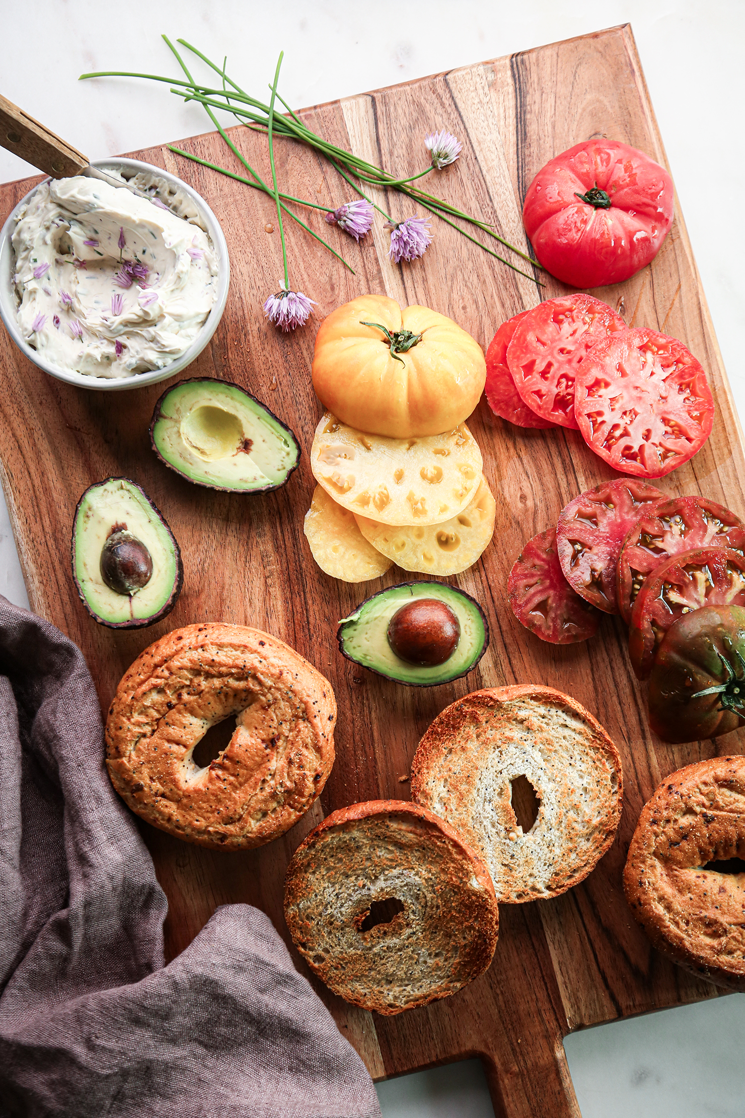 Avocado and Tomato Bagel Sandwich with chive and onion cream cheese ingredients on wooden board