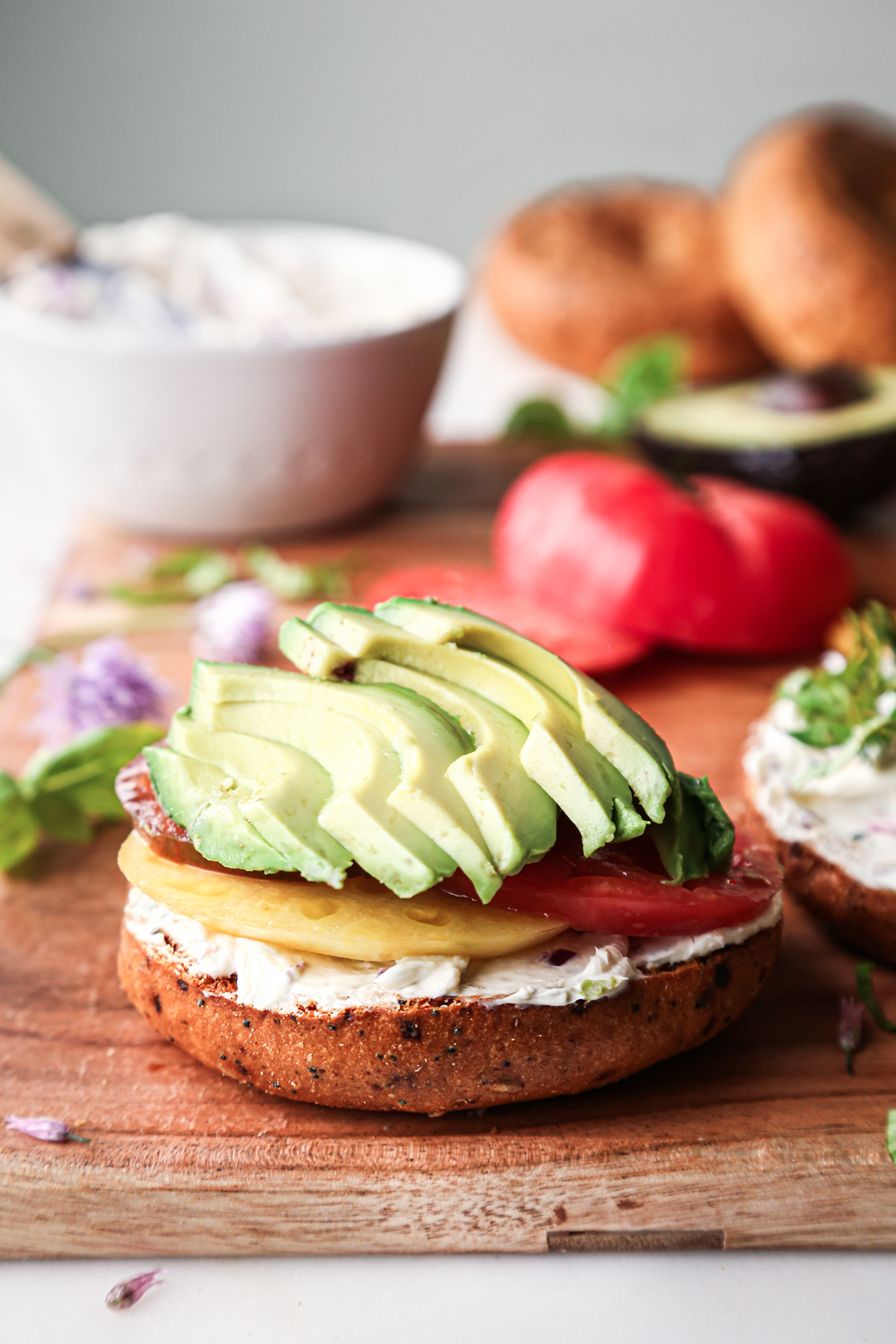 Avocado and Tomato slices layered on toasted bagel